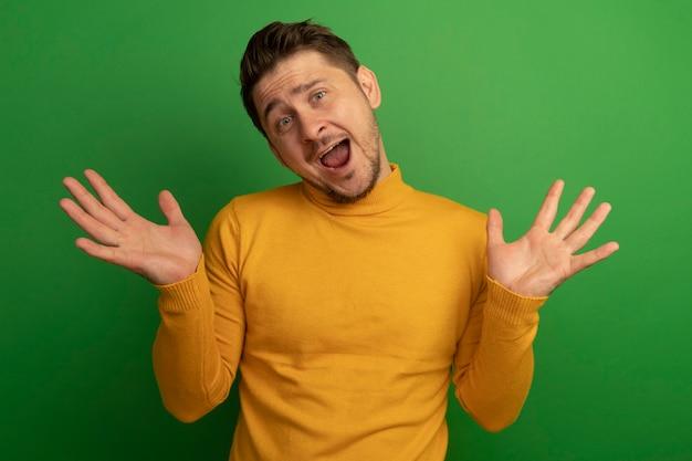 緑の壁に隔離された空の手を示す正面を見て感動した若いブロンドのハンサムな男