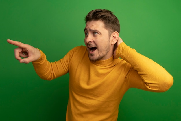 Impressionato giovane biondo bell'uomo che mette la mano dietro il collo guardando e indicando il lato isolato sul muro verde