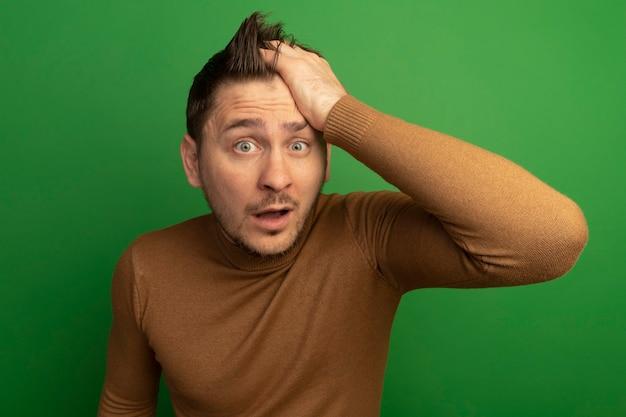 녹색 벽에 고립 된 전면을보고 머리에 손을 넣어 감동 젊은 금발의 잘 생긴 남자
