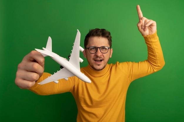 안경을 쓴 젊은 금발의 잘생긴 남자가 녹색 벽에 고립된 모습을 가리키는 모델 비행기를 쭉 뻗고 있다