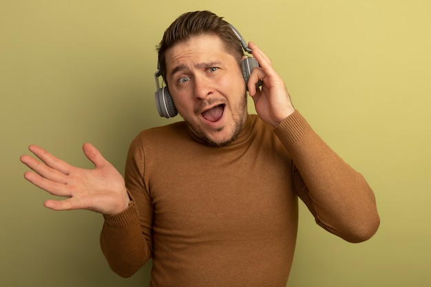 Impressed young blonde handsome man wearing and touching headphones looking  showing empty hand isolated on olive green wall