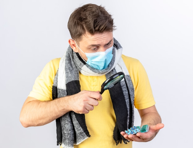 Impressed young blonde ill man wearing medical mask and scarf looks at packs of medical pills through magnifying glass isolated on white wall