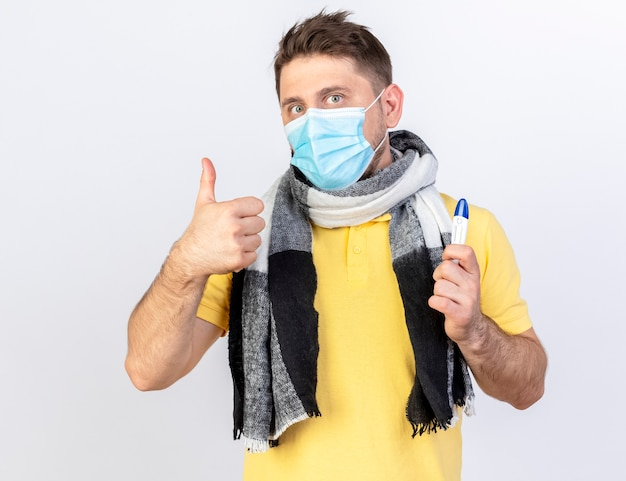 Impressed young blonde ill man wearing medical mask and scarf thumbs up and holds thermometer isolated on white wall