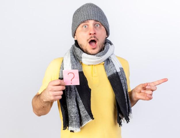 Впечатленный молодой блондин больной в зимней шапке и шарфе держит вопросительную записку и указывает в сторону, изолированную на белой стене