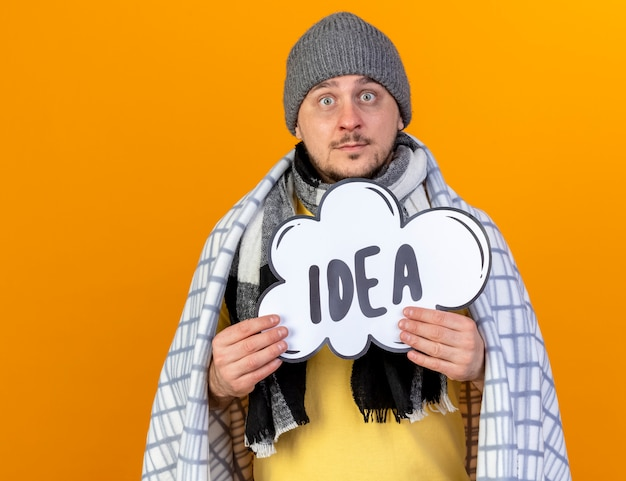 Impressed young blonde ill slavic man wearing winter hat and scarf wrapped in plaid holds idea bubble isolated on orange wall with copy space