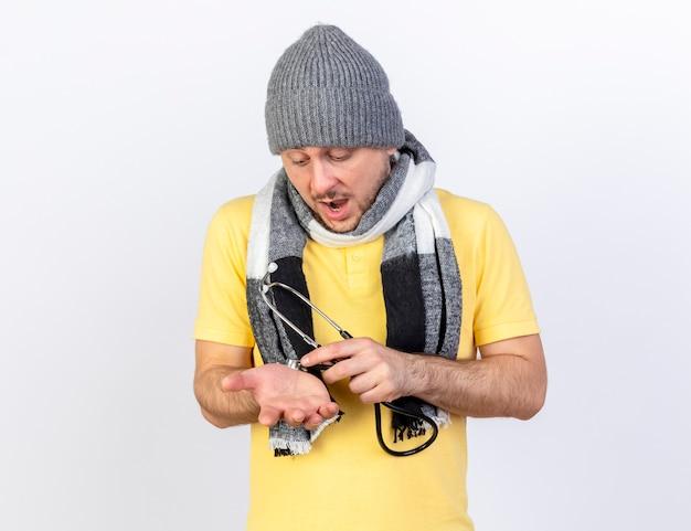 Impressionato giovane biondo slavo malato che indossa sciarpa e cappello invernale