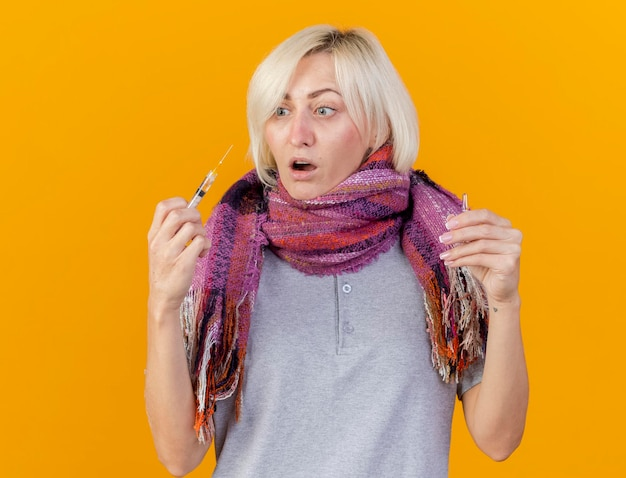 Impressed young blonde ill slavic woman wearing scarf holds ampoule