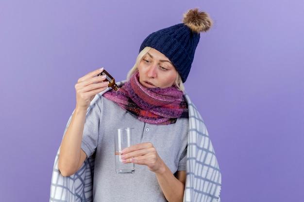 冬の帽子とスカーフを身に着けている感銘を受けた若い金髪の病気のスラブ女性