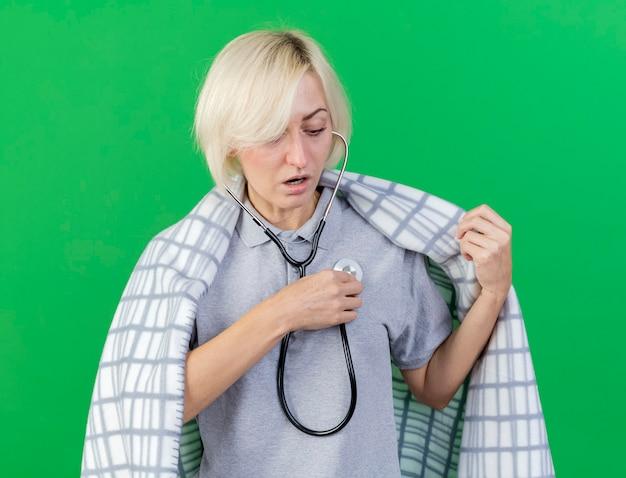 格子縞に包まれた印象的な若いブロンドの病気のスラブ女性は、コピースペースで緑の壁に隔離された聴診器を保持します