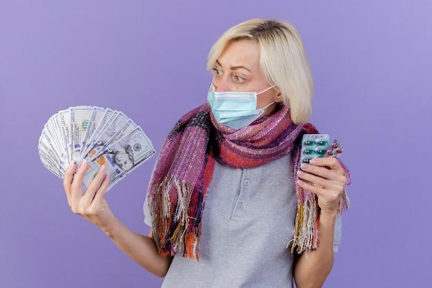 의료 마스크와 스카프를 착용하는 감동 된 젊은 금발의 아픈 여자는 보라색 벽에 고립 된 돈에 보이는 의료 약의 팩을 보유하고
