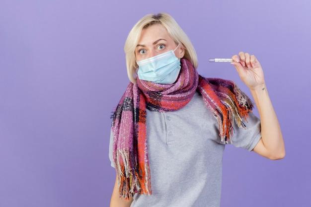 La giovane donna malata bionda colpita che indossa la maschera e la sciarpa mediche tiene il termometro isolato sulla parete viola