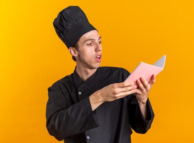 Colpito giovane maschio biondo cuoco in uniforme da chef e berretto lettura blocco note isolato su parete arancione