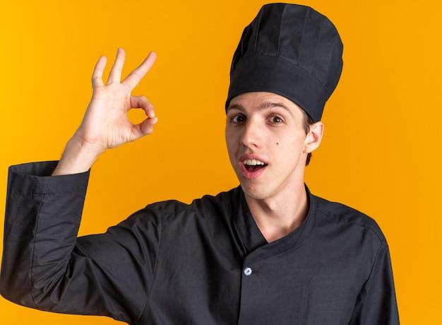 Впечатленный молодой блондин мужчина-повар в униформе шеф-повара и кепке, смотрящий в камеру, делает знак ок, изолированный на оранжевой стене