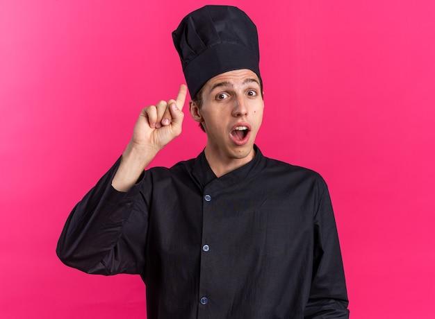 Впечатленный молодой блондин мужчина-повар в униформе и кепке шеф-повара смотрит в камеру, направленную вверх, изолированную на розовой стене