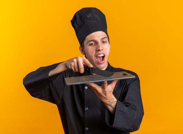 요리사 유니폼을 입은 젊은 금발 남성 요리사와 주황색 벽에 격리된 칼로 커팅 보드를 만지는 모자