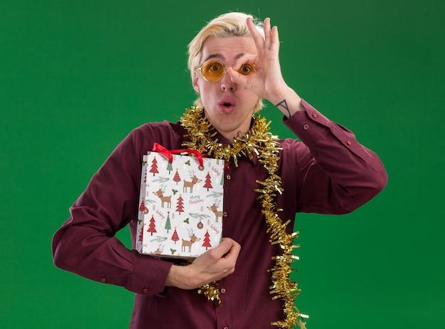 Впечатленный молодой блондин в очках с гирляндой из мишуры на шее, держащий рождественский подарочный пакет, делая жест, изолированный на зеленой стене