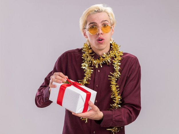 Impressed young blonde man wearing glasses with tinsel garland around neck holding gift package looking at camera isolated on white background