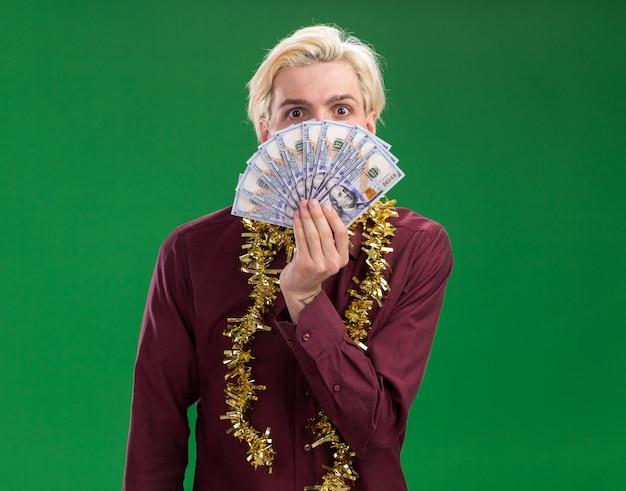 Impressionato giovane uomo biondo con gli occhiali con la ghirlanda di orpelli intorno al collo tenendo i soldi da dietro isolato sulla parete verde con spazio di copia