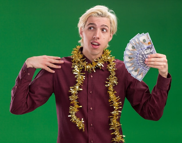 Impressed young blonde man wearing glasses with tinsel garland around neck holding money touching shoulder looking at side isolated on green background