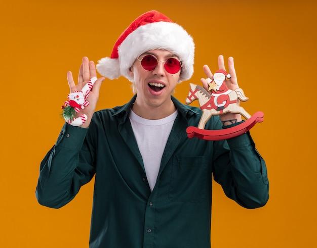 オレンジ色の背景に分離されたカメラを見て、ロッキングホースの置物と甘い杖の飾りにサンタを保持しているサンタの帽子とメガネを身に着けている印象的な若いブロンドの男