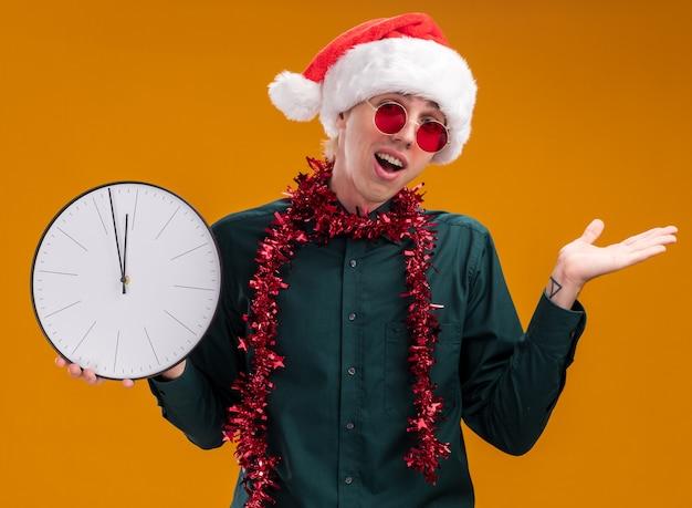 オレンジ色の背景で隔離の空の手を示すカメラを見て時計を保持している首の周りに見掛け倒しの花輪とサンタの帽子と眼鏡を身に着けている感動の若いブロンドの男