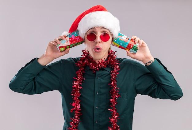 白い背景で隔離のカメラを見て秘密を聞いて耳の横にプラスチック製のクリスマスカップを保持している首の周りに見掛け倒しの花輪とサンタの帽子とメガネを身に着けている感動の若いブロンドの男