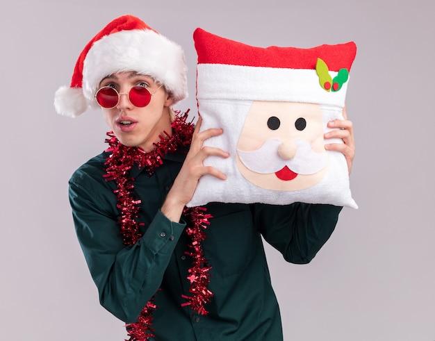 Впечатленный молодой блондин в шляпе санта-клауса и очках с гирляндой из мишуры на шее, держа подушку санта-клауса, глядя в камеру, изолированную на белом фоне