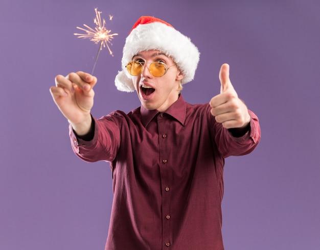Colpito il giovane uomo biondo che porta il cappello e gli occhiali della santa che tengono lo sparkler di festa che mostra il pollice su isolato sulla parete viola