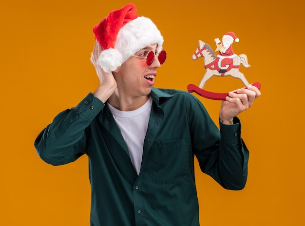 Impressed young blonde man wearing santa hat and glasses holding and looking at santa on rocking horse figurine keeping hand behind head isolated on orange background