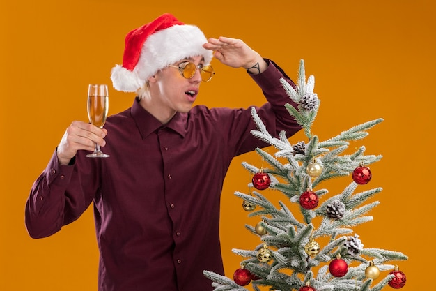 Impressed young blonde man wearing santa hat and glasses standing near decorated christmas tree holding glass of champagne looking at side into distance isolated on orange wall