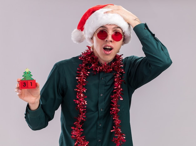 Impressed young blonde man wearing santa hat and glasses with tinsel garland around neck holding christmas tree toy with date looking at camera keeping hand on head isolated on white background