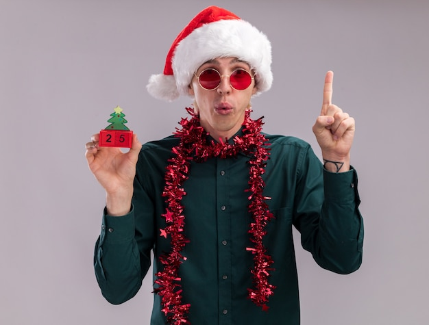 Impressed young blonde man wearing santa hat and glasses with tinsel garland around neck holding christmas tree toy with date looking at camera pointing up isolated on white background
