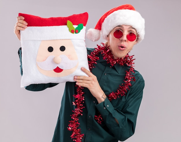 Impressed young blonde man wearing santa hat and glasses with tinsel garland around neck holding santa claus pillow looking at camera isolated on white background