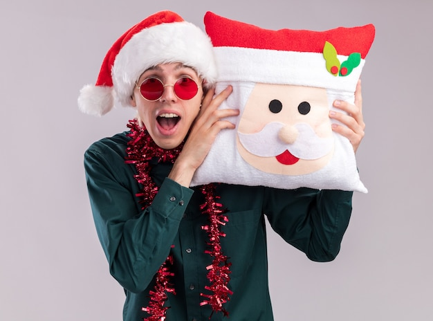 Impressed young blonde man wearing santa hat and glasses with tinsel garland around neck holding santa claus pillow touching head with it looking at camera isolated on white background