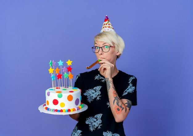 Впечатленная молодая белокурая тусовщица в очках и кепке на день рождения, держащая торт ко дню рождения со звездами, дует воздуходувку, смотрящую в камеру, изолированную на фиолетовом фоне с копией пространства