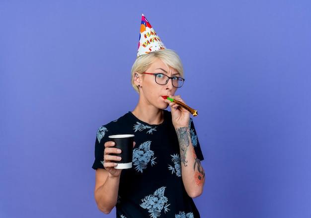 コピースペースで紫色の背景に分離されたカメラを見てガラスとプラスチック製のコーヒーカップ吹くパーティーブロワーを保持している誕生日キャップを身に着けている印象的な若いブロンドのパーティーの女の子