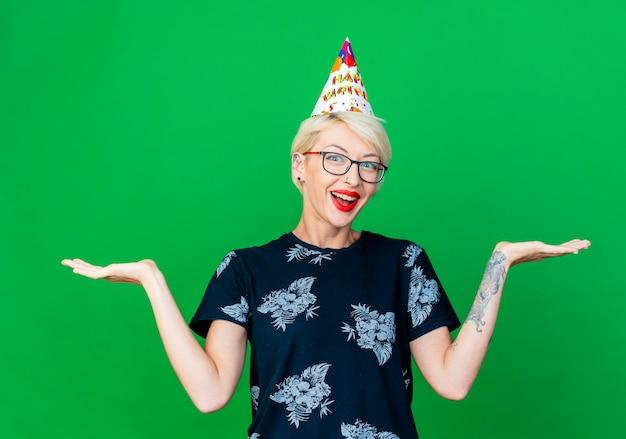 녹색 배경에 고립 된 빈 손을 보여주는 카메라를보고 안경과 생일 모자를 쓰고 감동 젊은 금발 파티 소녀