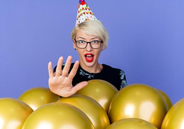 紫色の背景で隔離の停止ジェスチャーをしているカメラを見て風船の後ろに立っている眼鏡と誕生日の帽子を身に着けている感動の若いブロンドのパーティーの女の子