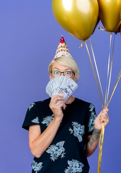 Impressed young blonde party girl wearing glasses and birthday cap holding balloons and money looking at camera from behind money isolated on purple background