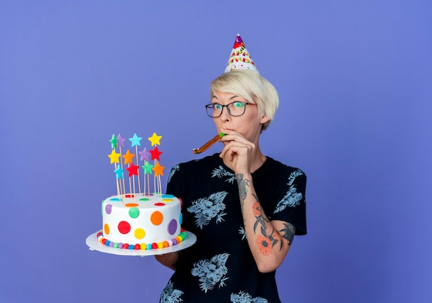 Impressed young blonde party girl wearing glasses and birthday cap holding birthday cake with stars blowing party blower looking at camera isolated on purple background with copy space