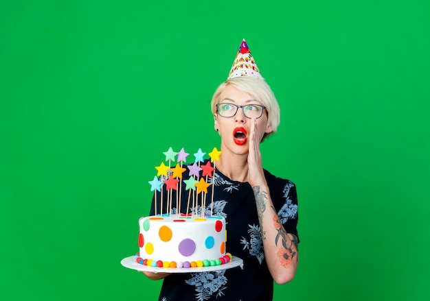 Impressed young blonde party girl wearing glasses and birthday cap holding birthday cake with stars looking at side whispering isolated on green background with copy space