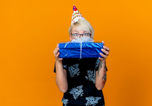 Impressed young blonde party girl wearing glasses and birthday cap holding gift box looking at camera from behind it isolated on orange background with copy space