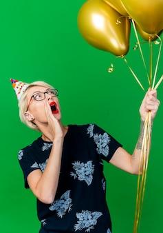 Impressionato giovane ragazza bionda festa con gli occhiali e cappello di compleanno tenendo e guardando i palloncini tenendo la mano vicino alla bocca chiamando fuori isolato su sfondo verde