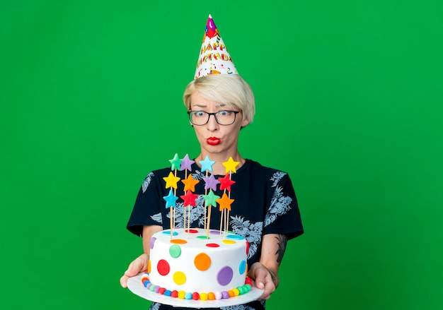 Impressed young blonde party girl wearing glasses and birthday cap holding and looking at birthday cake isolated on green background with copy space