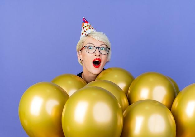 Impressionato giovane ragazza bionda festa con gli occhiali e berretto di compleanno in piedi dietro i palloncini che guarda l'obbiettivo isolato su sfondo viola
