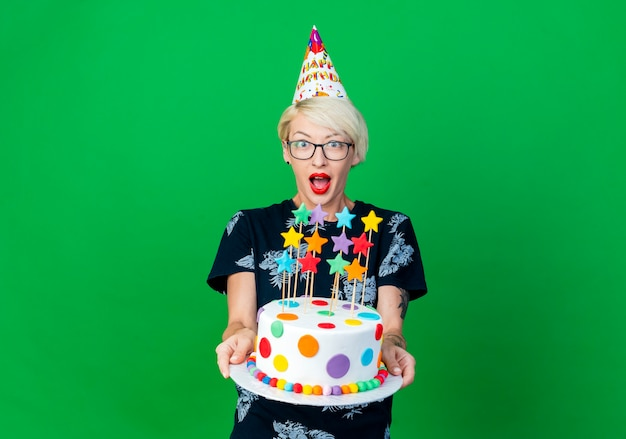 Impressed young blonde party girl wearing glasses and birthday cap stretching out birthday cake with stars looking at camera isolated on green background with copy space