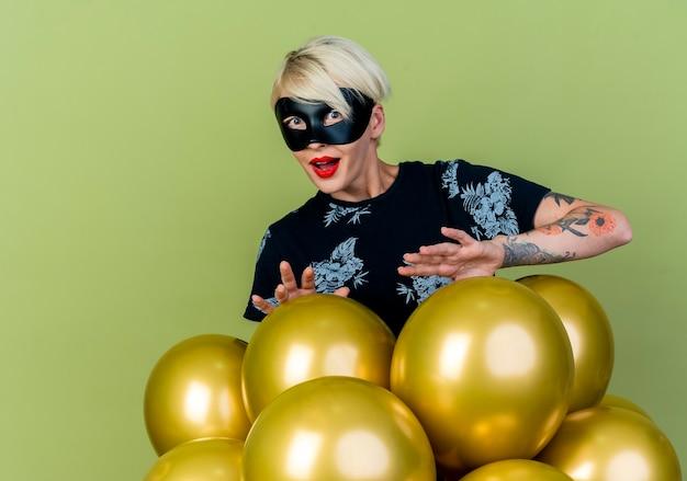 Impressionato giovane bionda party girl indossando la maschera di travestimento in piedi dietro i palloncini guardando la telecamera mantenendo le mani sopra di loro isolato su sfondo verde oliva con spazio di copia