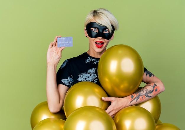 Impressionato giovane ragazza bionda party indossando la maschera di travestimento in piedi dietro i palloncini che mostra la carta di credito guardando la telecamera isolata su sfondo verde oliva