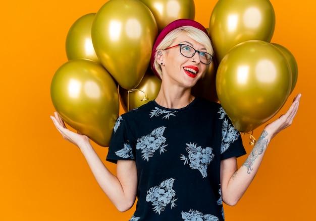 オレンジ色の背景で隔離の側を見てそれらに触れる風船の前に立っているパーティー帽子と眼鏡を身に着けている感動の若いブロンドのパーティーの女の子