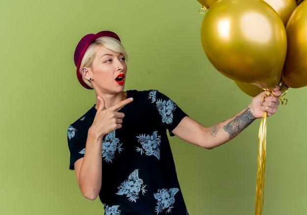 Impressionato giovane ragazza bionda party indossando il cappello del partito che tiene guardando e indicando palloncini isolati su sfondo verde oliva con lo spazio della copia